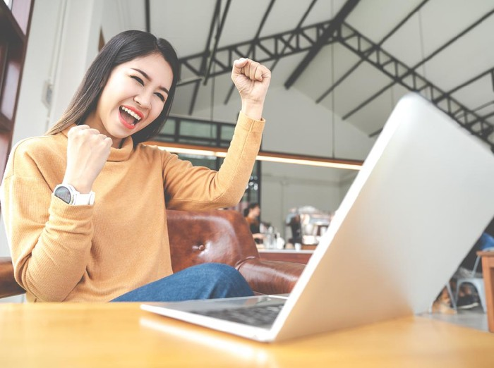 Young attractive asian woman looking at laptop computer feeling happy cheerful or excited expression success or win sitting on desk table in cafe coffee shop in wide close up view with soft tone.