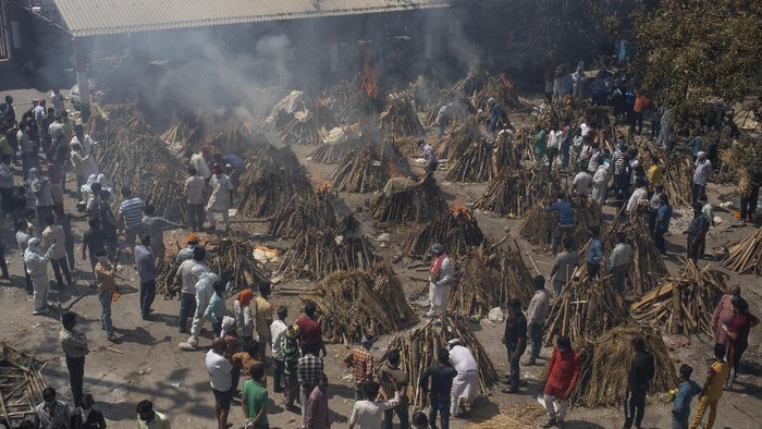 People perform rituals next to a funeral pyre for a family member who died of COVID-19 at a ground that has been converted into a crematorium for mass cremation of COVID-19 victims in New Delhi, India, Saturday, April 24, 2021. Delhi has been cremating so many bodies of coronavirus victims that authorities are getting requests to start cutting down trees in city parks, as a second record surge has brought Indias tattered healthcare system to its knees.(AP Photo/Altaf Qadri)