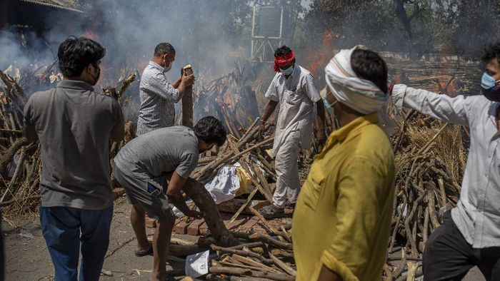 People perform rituals next to a funeral pyre for a family member who died of COVID-19 at a ground that has been converted into a crematorium for mass cremation of COVID-19 victims in New Delhi, India, Saturday, April 24, 2021. Delhi has been cremating so many bodies of coronavirus victims that authorities are getting requests to start cutting down trees in city parks, as a second record surge has brought Indias tattered healthcare system to its knees. (AP Photo/Altaf Qadri)