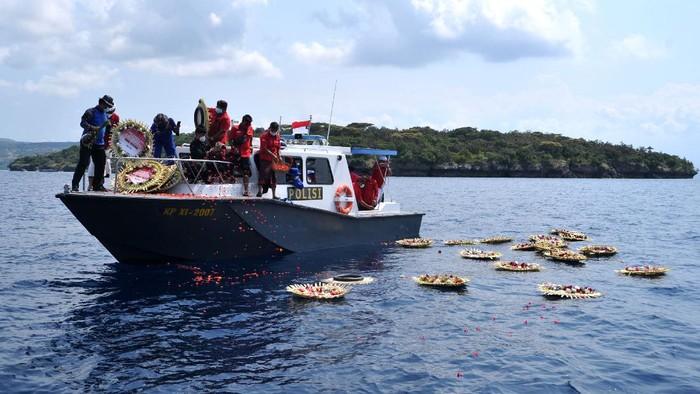 Sejumlah pejabat menaburkan bunga dan melemparkan karangan bunga saat kegiatan Doa dan Tabur Bunga untuk KRI Nanggala 402 di perairan utara Bali, Buleleng, Bali, Senin (26/4/2021). Kegiatan tersebut dilakukan untuk mendoakan dan memberikan penghormatan bagi seluruh awak KRI Nanggala 402 yang gugur setelah kapal selam tersebut dipastikan tenggelam di perairan utara Bali. ANTARA FOTO/Fikri Yusuf/hp.