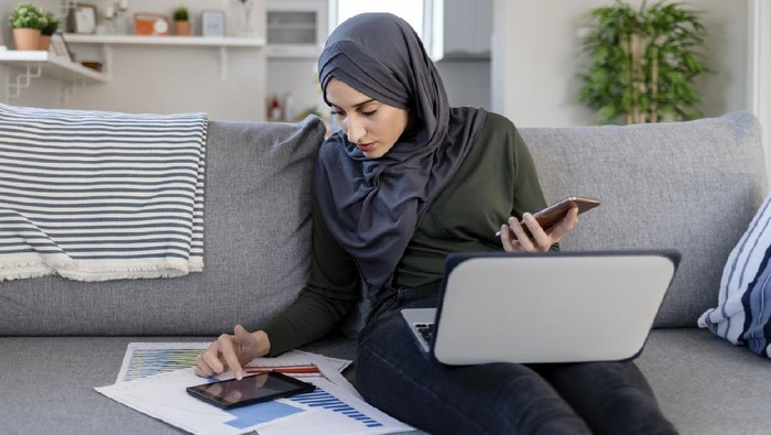 Focused Young Muslim Female Entrepreneur Wearing a Hijab Reading Through Paperwork While Working in Her Home Office. Work Opportunities For Muslim Women Concept. Freelance Concept.