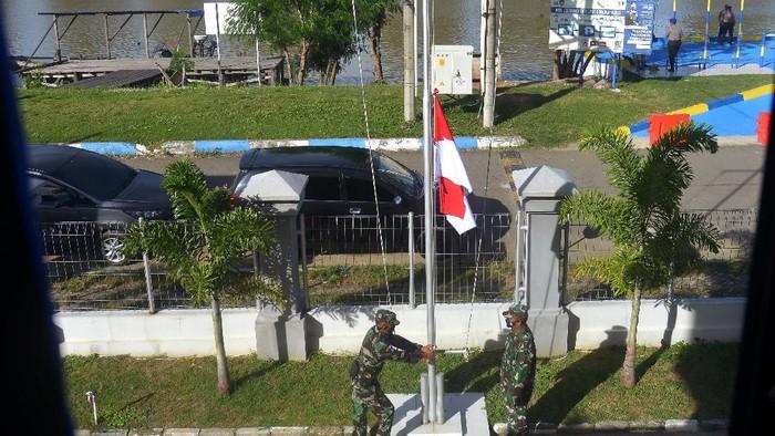 Prajurit Yon Taifib 2 Marinir TNI AL mengibarkan bendera merah putih setengah tiang di posko mereka di Pelabuhan Tanjung Wangi, Banyuwangi, Jawa Timur, Senin (25/4/2021). TNI AL mengibarkan bendera setengah tiang untuk menghormati 53 awak kapal selam KRI Nanggala-402 yang gugur di perairan Bali dan bendera setengah tiang tersebut akan dikibarkan selama 7 hari. ANTARA FOTO/Zabur Karuru/hp.