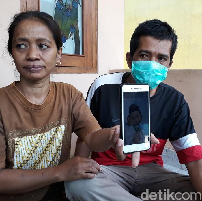 Driver ojol, Bandiman dan istrinya menunjukkan foto buah hatinya yang meninggal usai makan paket takjil misterius