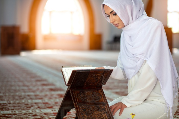 Young Muslim woman praying in mosque with Quran.