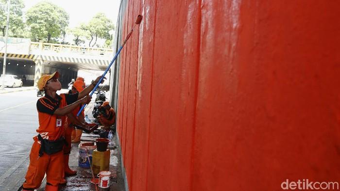 Sejumlah petugas menata dinding kolong jembatan Tanah Abang, Jakarta Pusat, agar terlihat bersih dengan melakukan pengecatan baru berwarna oranye.
