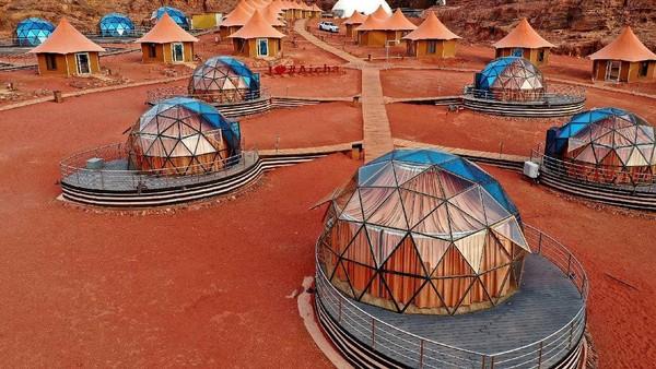 Kamarnya berupa suite kaca yang cantik, dari jauh tampak perpaduan warna biru dan oranye. Dari dalam, traveler bisa melihat gurun Wadi Rum yang unik. (Memories Aicha Luxury Camp/Instagram)