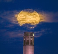 A pink supermoon rises in the night sky over Coit Tower in San Francisco on Monday, April 26, 2021. The full moon in April is known as the