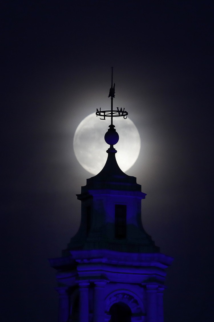 The moon rises through cloud over County Hall in London, Monday, April 26, 2021. This moon is a supermoon, meaning it appears larger than an average full moon because it nearer the closest point of its orbit to Earth. (AP Photo/Kirsty Wigglesworth)