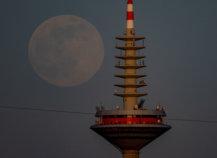 The full moon rises behind the television tower in Frankfurt, Germany, Monday, April 26, 2021. (AP Photo/Michael Probst)
