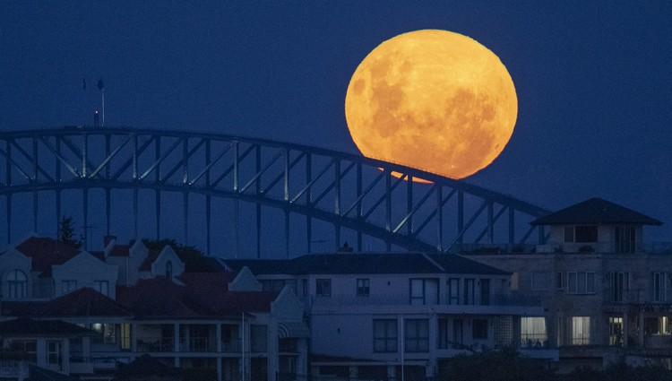 The moon rises over the Sydney Harbour Bridge in Australia, Tuesday, April 27, 2021. This moon is a supermoon, meaning it appears larger than an average full moon because it is nearer the closest point of its orbit to Earth. (AP Photo/Mark Baker)