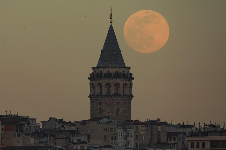 The full moon rises behind Istanbuls iconic Galata Tower, Monday, April 26, 2021. (AP Photo/Emrah Gurel)