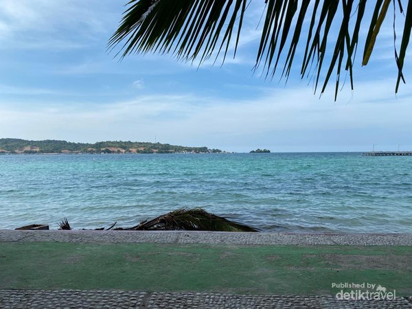 Biru langit dan laut yang bersinergi di antara horizontal daratan utama Pulau Bokori.