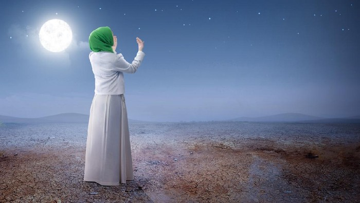 Rear view of asian muslim woman in veil raised hands and praying on the sand dune with moon and night scene background
