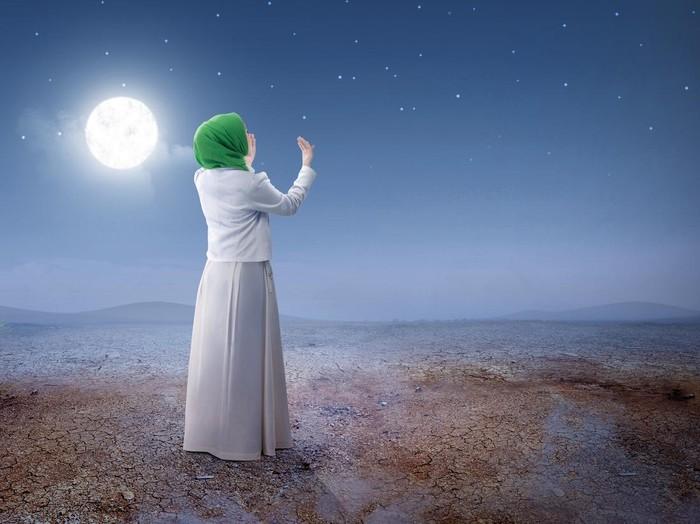 Muslim woman pray on hijab praying with Koran on mat indoors