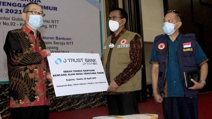 Direktur Utama J-Trust Bank Ritsuo Fukadai (kiri) disaksikan Karo Humas Pmeprov NTT Marius A Jelamu (kanan)  menyerahkan secara simbolis bantuan  bencana alam kepada Sekda NTT Beneditus Polo Maing di Posko Tanggap Darurat Bencana Siklon Tropis Seroja di Kota Kupang, NTT, Kamis (29/4). Bantuan berupa makanan bayi, obat-obaran, maske dan selimut itu akan disalurkan ke seluruh provinsi di NTT yang mengalami bencana alam akibat Siklon Tropis Seroja pada 3-4 April lalu.