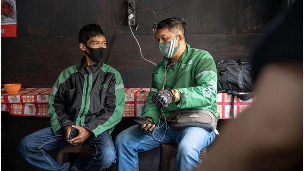 Mitra pengantaran GrabFood sedang menunggu makanan di salah satu merchant di Jayapura. Layanan GrabFood membuka kesempatan kerja bagi merchant maupun mitra pengantaran.