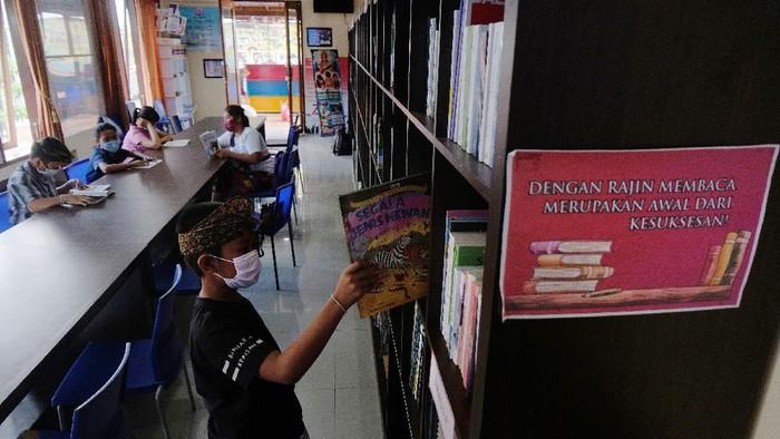 Siswa belajar secara daring dengan memanfaatkan fasilitas wifi gratis di perpustakaan desa.