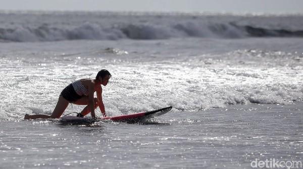 Wisatawan berlatih surfing di Pantai Parerenan, Canggu, Bali.