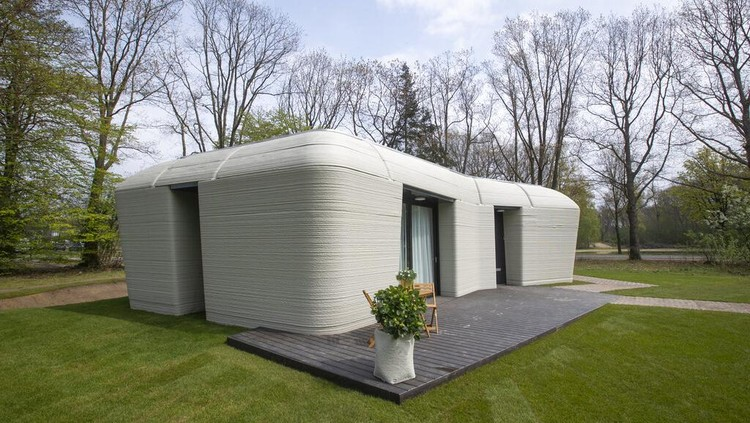 View of the living room with the open kitchen showing the printer layers in the walls of the 3D-printed 94-square meters (1,011-square feet) two-bedroom bungalow resembling a boulder with windows in Eindhoven, Netherlands, Friday, April 30, 2021. The fluid, curving lines of its gray walls look natural. But they are actually at the cutting edge of housing construction in the Netherlands and around the world. They were 3D printed at a nearby factory. (AP Photo/Peter Dejong)