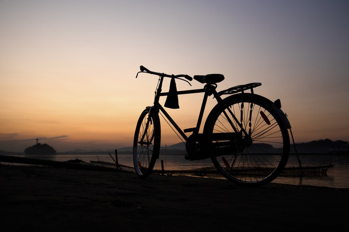 A bicycle in the banks of Brahmaputra river at sunset