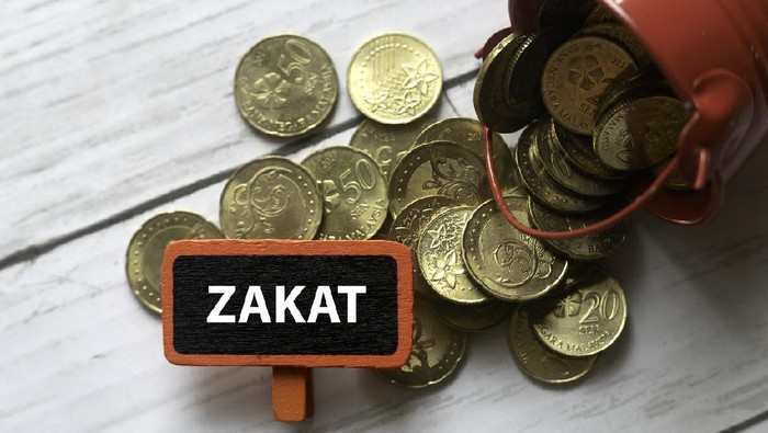 Selective focus of red bucket full with gold coins and red tag written with ZAKAT on white wooden background.