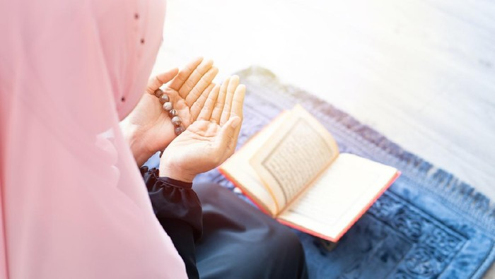 side of asian young beautiful muslim woman pray with beads and read quran sit on carpet mat with meditation in mosque.