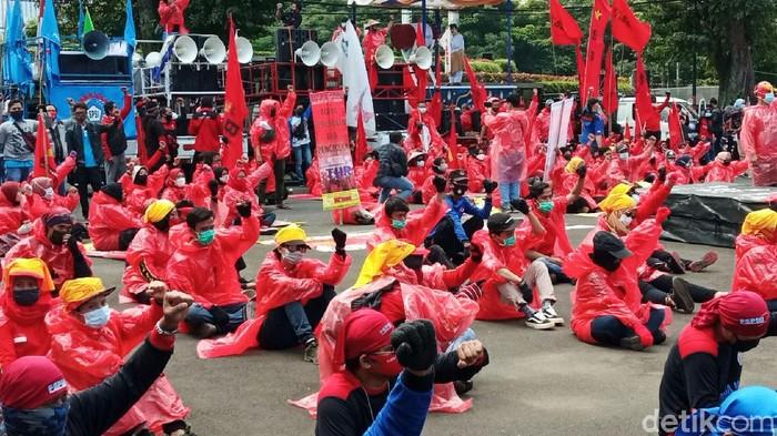 Aksi turun ke jalan yang dilakukan massa buruh memperingati hari buruh atau May Day saling mengingatkan protokol kesehatan. Bahkan salah satu kelompok massa buruh berdemo menggunakan alat pelindung diri (APD).
