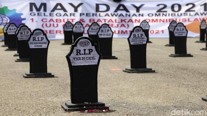 Massa buruh memperingati May Day 2021 dengan menggelar aksi di kawasan Patung Kuda, Jakarta. Mereka juga membawa beberapa nisan bertuliskan aspirasi.