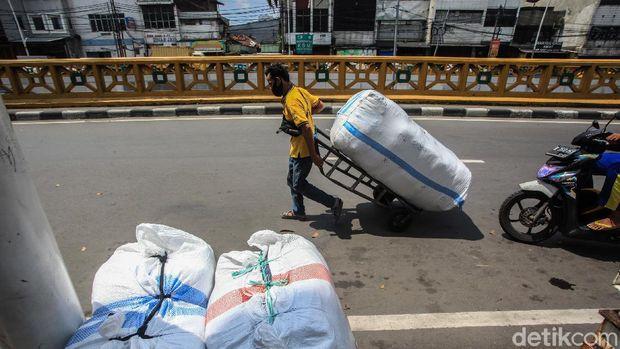 Sejumlah buruh panggul hilir-mudik di Pasar Tanah Abang, Jakarta, Sabtu (1/5/2021). Pada masa pandemi, pendapatan buruh panggul turun drastis dari menjadi sekitar Rp 100.000/hari.