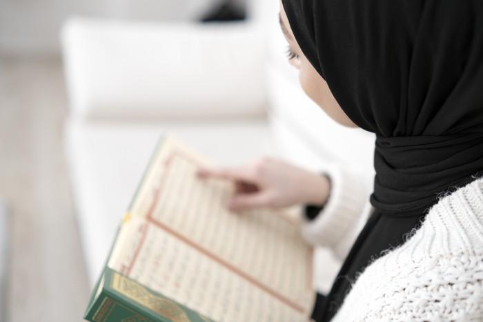 Muslim young woman reading Koran. Horizontal composition.
