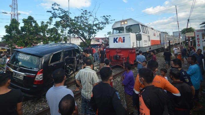 Warga melihat kondisi mobil yang tertabrak Kereta Api (KA) Sibinuang jurusan Naras - Padang di Lubuk Buaya, Padang, Sumatera Barat, Minggu (2/5/2021). Akibat kejadian tersebut pengemudi mobil mengalami luka-luka serta terganggunya jadwal keberangkatan kereta, sementara itu PT KAI Divre II Sumbar mencatat sedikitnya 15 kasus kecelakaan terjadi pada awal 2021 di perlintasan sebidang rel kereta api. ANTARA FOTO/Iggoy el Fitra/wsj.