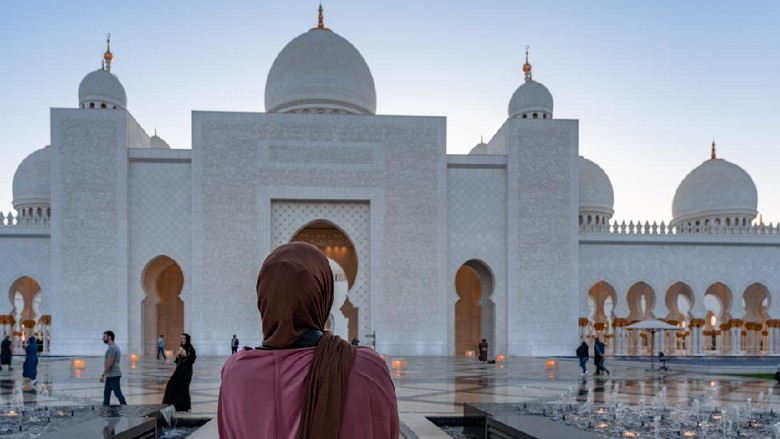 Woman in Hijab looking at a  mosque at sunset | Abu Dhabi Sheik Zayed Mosque | Beautiful islamic architecture | Tourist attraction - Abu Dhabi, UAE, March 22, 2020