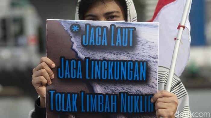 Peserta aksi memajang spanduk Tolak Pembuangan Limbah Nuklir Fukushima di Laut di Kawasan Patung Kuda, Jakarta, Senin (3/5/2021). Pembuangan limbah nuklir berpotensi menimbulkan pencemaran lingkungan laut.