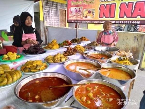 Uni penjual Nasi Kapau menunggu pembeli di hadapan hidangannya