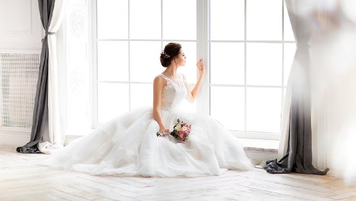 Young beautiful brunette woman with bouquet posing in a wedding dress