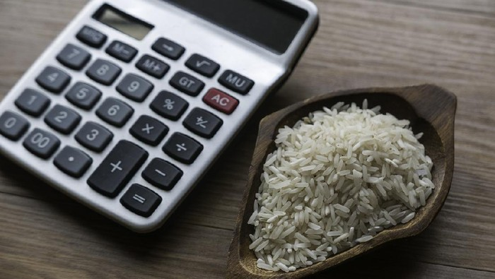 Selective focus of rice and calculator on wooden background.