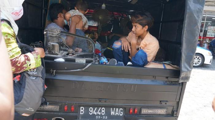 Polisi menghentikan pemudik naik pikap yang ditutup terpal di Jalan Lingkar Demak, Senin (3/5/2021).