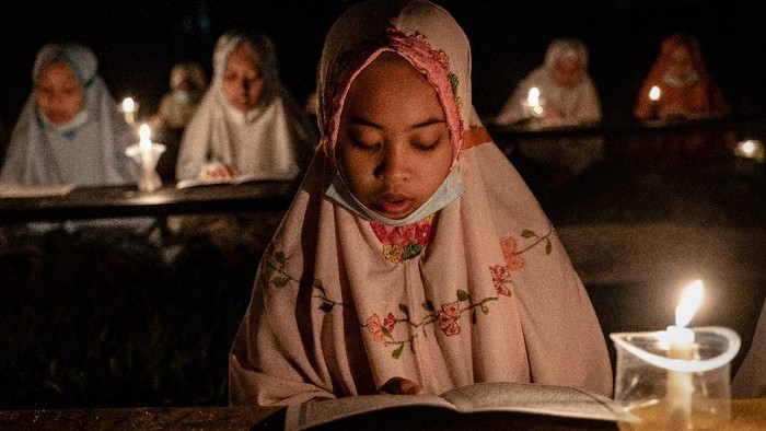 BOYOLALI, INDONESIA - MAY 02: A student prays after read the Quran by candlelight during ritual Nuzulul Quran and Laylat al-Qadr (Night of Destiny) which marks the night in which the holy Quran was first revealed to the Prophet Mohammed at the Nurul Hidayah Al-Mubarokah boarding school on May 2, 2021 in Boyolali, Central Java, Indonesia. Laylat al-Qadr is was one of the odd-numbered nights of the last ten days of Ramadan. Ramadan, the ninth month of the Islamic calendar is a month of fasting, prayers and recitation of the Quran. (Photo by Ulet Ifansasti/Getty Images)