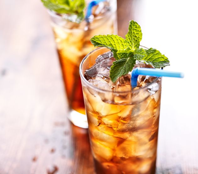 iced tea with blue straw and mint garnish , shot with selective focus.