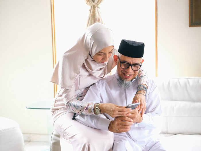Father and daughter looking at phone during raya celebration in Malaysia