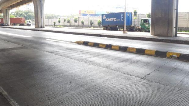 Pembatas jalan di Jl Raya Cilincing Raya di depan New Priok Common Gate usai sebulan dicat ulang.
