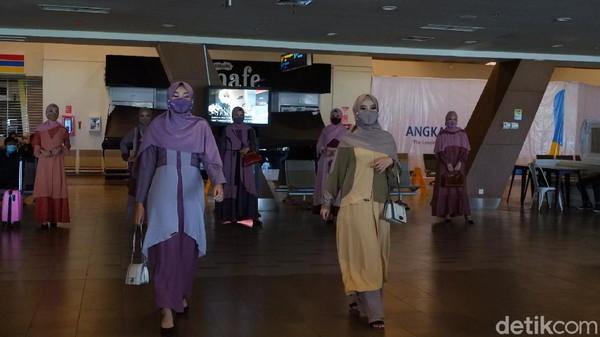 Para model, eh, karyawan bandara ini berjalan sambil memamerkan busana muslim yang mereka kenakan di area keberangkatan (departure). Para calon penumpang pun merasa terhibur dengan penampilan mereka.