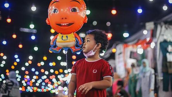 Seorang anak memegang balon di bazar Ramadhan di Kuala Lumpur, Malaysia.