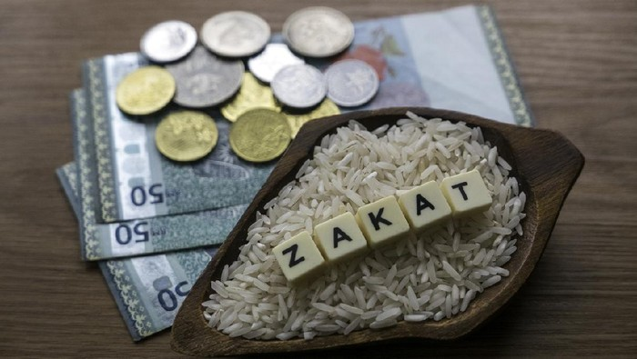 Concept of zakat in Islam religion. Selective focus of money and rice with alphabet of zakat on wooden background.