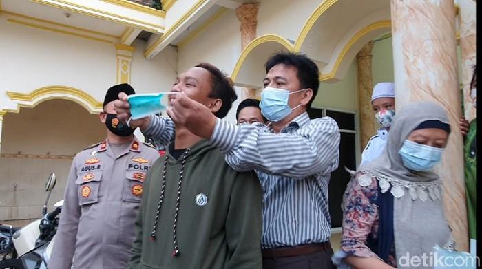 Kini, Roni memasangkan masker ke Nawir sebagai simbol keduanya telah berdamai.