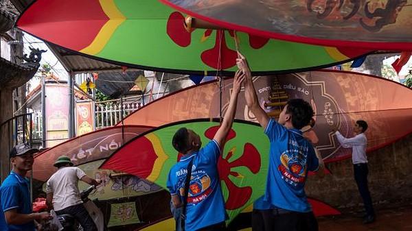Pemain mempersiapkan layang-layang mereka untuk kompetisi selama festival layang-layang tradisional di desa Ba Duong Noi di Hanoi, Vietnam.