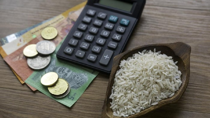 Selective focus of rice, money, coins and calculator on wooden background.