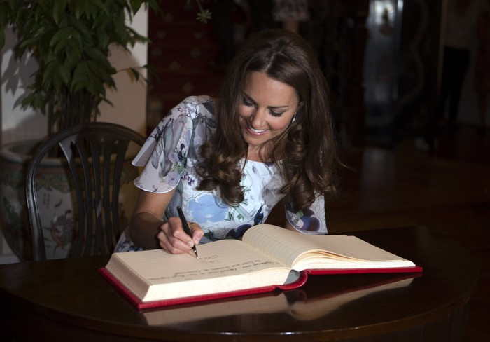 SINGAPORE - SEPTEMBER 12: Catherine, Duchess of Cambridge signs the visitors book as she and her husband, Prince William, Duke of Cambridge (not pitured) visit the British High Commissioners residence, Eden Hall, on day 2 of the Diamond Jubilee Tour of the Far East on September 12, 2012 in Singapore. The Duke and Duchess of Cambridge are on a Diamond Jubilee Tour of the Far East taking in Singapore, Malaysia, the Solomon Islands and the tiny Pacific Island of Tuvalu. (Photo by Ian Vogler - Pool/Getty Images)