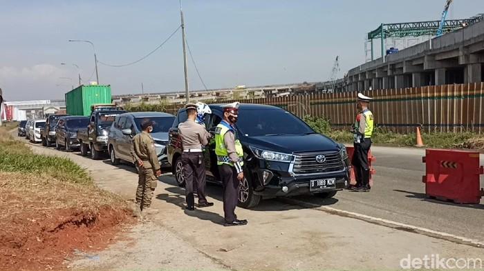 Petugas memeriksa kendaraan yang keluar Tol Cileunyi, Kabupaten Bandung.