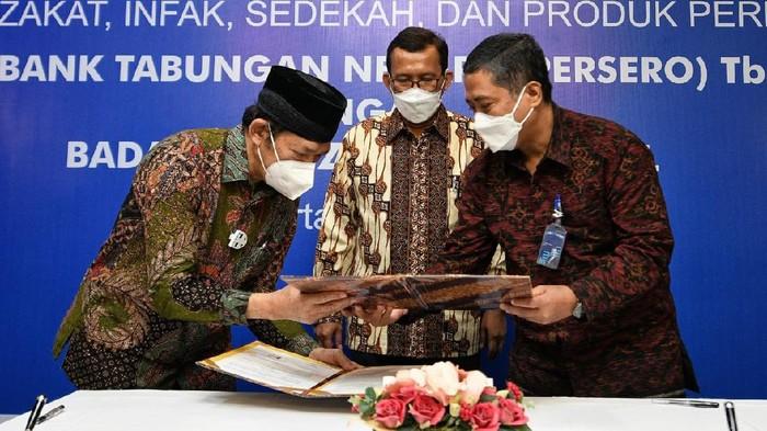 Direktur Utama PT Bank Tabungan Negara (Persero) Tbk. Haru Koesmahargyo (tengah) menyaksikan Nota Kesepahaman yang ditandatangani Direktur Consumer and Commercial Lending Bank BTN Hirwandi Gafar (kanan) dan Ketua Badan Amil Zakat Nasional (BAZNAS) Noor Achmad pada acara Penandatanganan Nota Kesepahaman antara Bank BTN dan Baznas di Jakarta, Jumat (7/5). BTN Syariah melakukan sinergi dengan BAZNAS untuk mengembangkan ekosistem layanan zakat, infak, dan sedekah sehingga pembayarannya menjadi lebih mudah. Selain menawarkan kemudahan pembayaran zakat, infak, dan sedekah, BTN Syariah juga menawarkan produk dan layanan perbankan lainnya untuk dapat mengoptimalkan kinerja BAZNAS. Bank BTN juga memberikan fasilitas pembiayaan termasuk KPR Syariah bagi para pengurus BAZNAS sehingga dapat memiliki hunian sendiri.